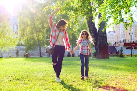 Mom and daughter holding hands walking in the park