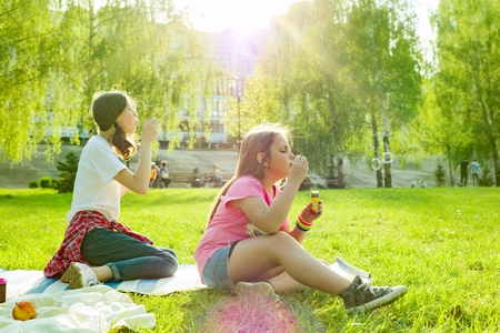 Adolescent girls having fun in the park - blowing soap bubbles