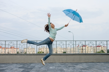 Girl is flying with an umbrella, city background.