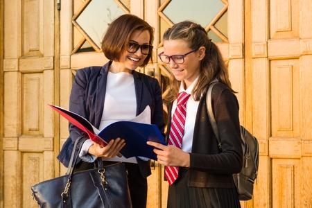 Outdoor portrait of high school teacher with schoolgirl near the front door of the school.