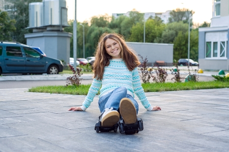 Girl teenager in the wheels of rollers, adapted to sneakers. Urban background Stock Photo