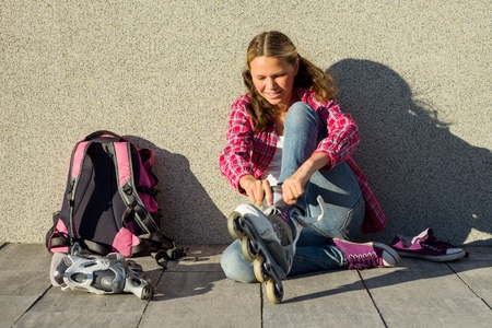 Active sports teen gir in quad roller skates, urban background. Teenage girl removes sneakers and clothes roller skates outdoor. Sits on a wall background, next to her backpack