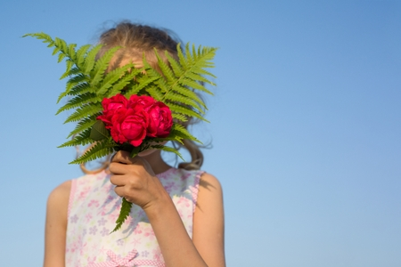 Child girl holding bouquet of rose flowers. Gift, surprise, spring summer family holiday. Blue sky background, copy space