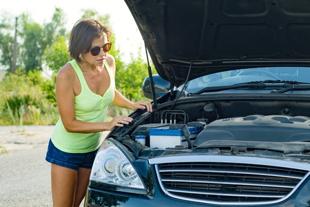 Frustrated woman driver stands near broken car on country road, looks at problem, an open hood.