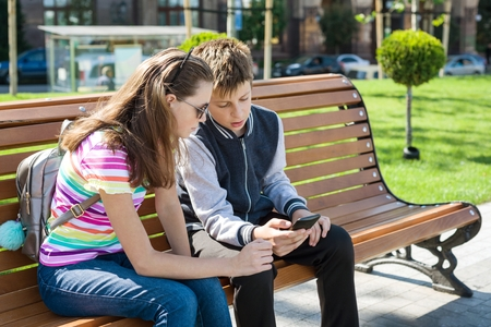 Boy and girl teenagers play, read, look at the smartphone. On the bench, the urban background. Stock Photo