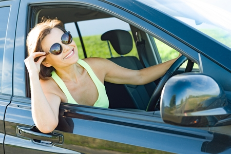 Beautiful female driver smiling while driving his car. Stock Photo