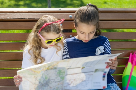 Outdoors portrait children tourists. With map of city on the bench.