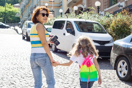 Urban portrait of parent and child. Mother and daughter hold hands, walk around the city, back view. Stock Photo
