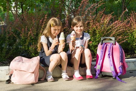 Portrait of two girlfriends schoolgirls 7 years old in school uniform with backpacks eating ice cream.