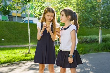 Portrait of two girlfriends schoolgirls 7 years old in school uniform eating ice cream. Background city, summer, sidewalk, decorative bushes. Banque d'images