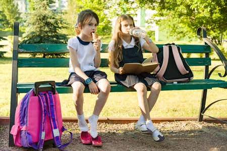 Attractive little girlfriends schoolgirls with backpacks, Girls rest on bench in the park after school, eat ice cream, drink water, read book, talk Banque d'images