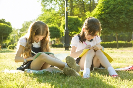 Two little girl friends schoolgirl learns sitting on a meadow in the park. Children with backpacks, books, notebooks