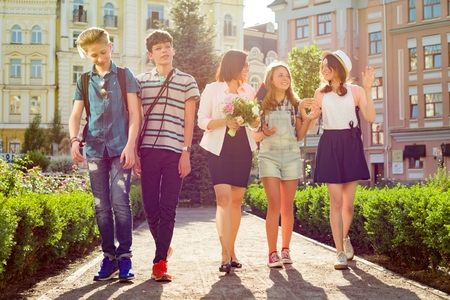Children teenagers go with their teacher. The students congratulated female with bouquet of flowers. Teacher's Day. Stock fotó