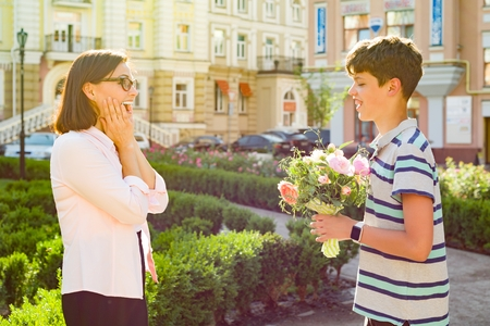 Son teenager congratulated mother with a surprise bouquet of flowers. Stock fotó