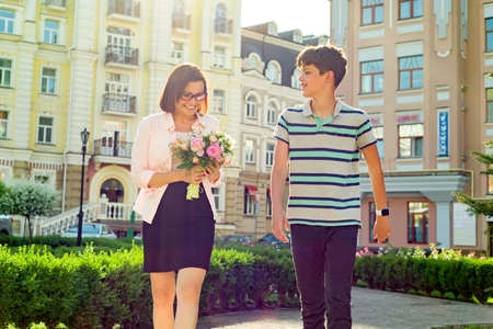 Portrait of woman with bouquets of flowers and teenage boy on city background. Son congratulated his mother.