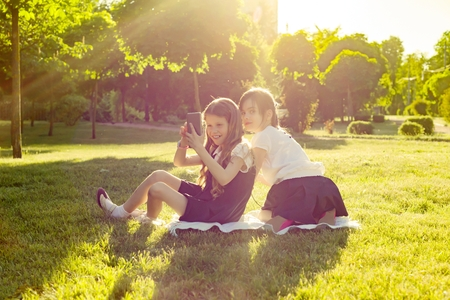 Cheerful little girl friends play with smartphone sitting on a meadow in the park. The concept of people, children, technology, friends and friendship.