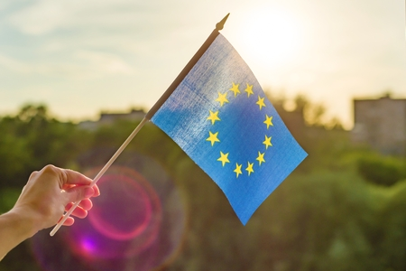 Hand holds European Union flag in an open window. Background blue sky, silhouette of the city, sunset.