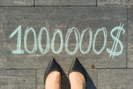 View from above, female feet with text 1000000 dollar written on grey sidewalk Stock Photo