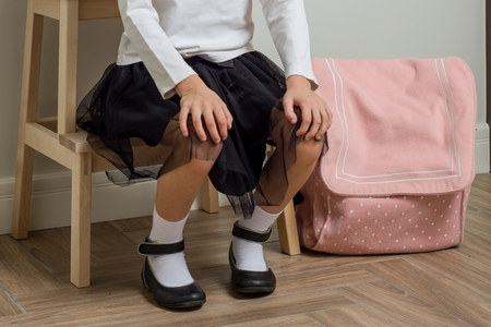 Child little girl going to school, at home with backpack sitting on chair in the hallway near the front door.