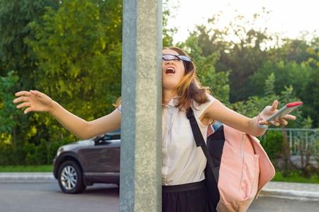Portret van een jong onoplettend meisje, afgeleid door mobiele telefoon. Meisje crashte tegen straatpost, telefoon liet vallen Stockfoto