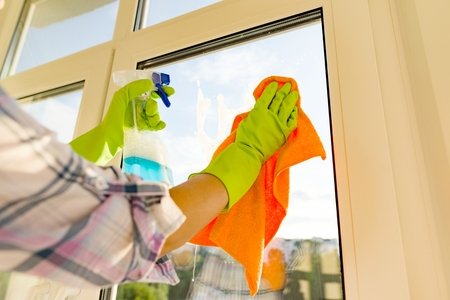 Close-up of woman cleaning windows, hands in rubber protective gloves, rag and detergent sprayer Stock Photo