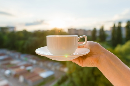 A female hand holding a white cup and saucer with the evening sunset in the city background