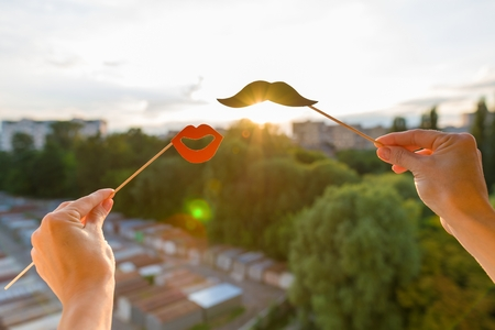 Red lips and black mustache with the evening sunset in the city background Banco de Imagens