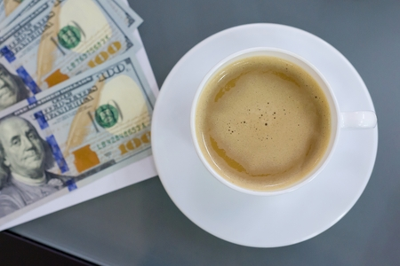 Top view of a cup of coffee and money on the table Banco de Imagens