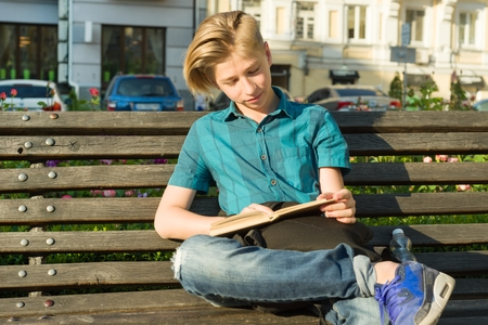 Outdoor portrait of a teenage boy and girl 14, 15 years old, sitting on bench in city park with book Standard-Bild