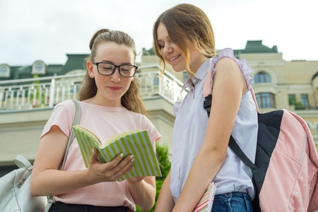 Portrait of two schoolgirls of teenagers with school backpacks and books.