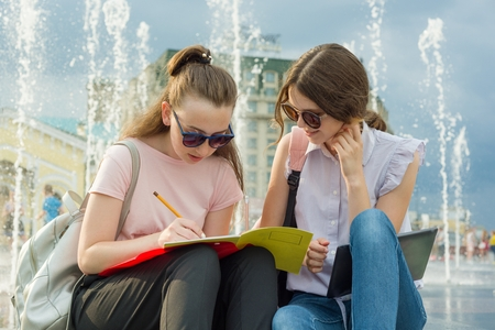 Outdoor portrait of young girls student with backpacks, books are sitting near the city fountain. Talking, learning Banco de Imagens