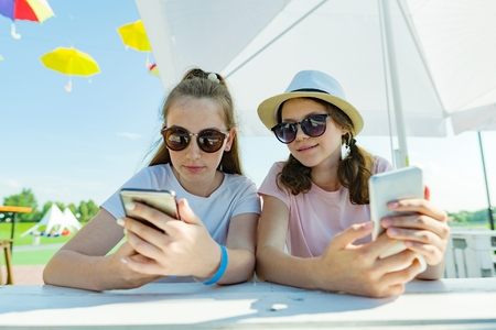 Young teen girls with mobile phones. Sit in a street cafe, sunny summer day in recreation and entertainment area