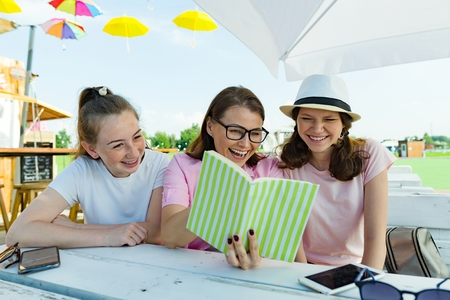 Mom and daughters teenagers have fun, look and read funny book. Communication of the parent and children of adolescents. Sit in a street cafe, sunny summer day in recreation and entertainment area