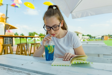 Young teen girl with glasses drinking blue lemonade and reading book in an outdoor cafe. Background green area of rest and entertainment