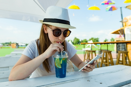 Summer holidays, rest. Teenage girl of 16 years in hat and sunglasses with blue lemonade sits at table in summer street cafe. Background green area of rest and entertainment