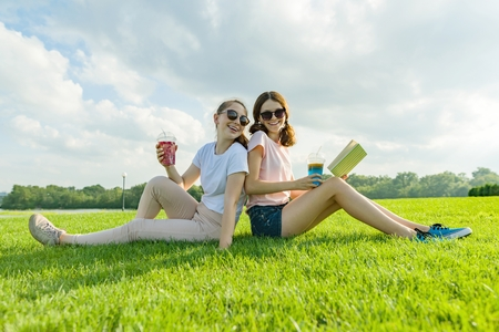 Summer sunny day, two girlfriends teenagers sit on green lawn, drink cocktails, talk, read book, laugh, have fun