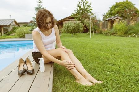Reife Geschäftsfrau nach einem Arbeitstag sitzt in der Nähe des Pools zu Hause. Sie zog ihre Schuhe aus und schmierte ihre Füße mit beruhigender Fußcreme