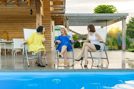 Three mature middle-aged women are having fun and talking, sitting in a lounger by the pool, summer evening
