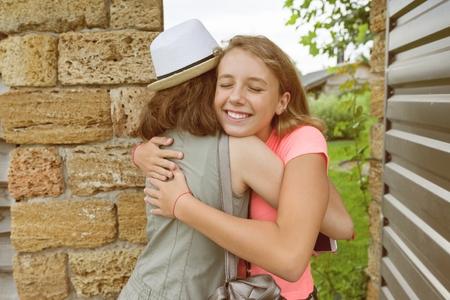 Girl opens front door, girlfriends greeted, hugs at the meeting