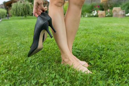 Female barefooted legs on green lawn, woman holding classic heeled shoes. End of the working day, rest, fatigue Stock Photo