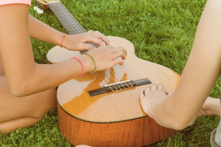 Group of happy teenage girls having fun outdoors with guitar. Come up with new music, sit on green lawn in the yard