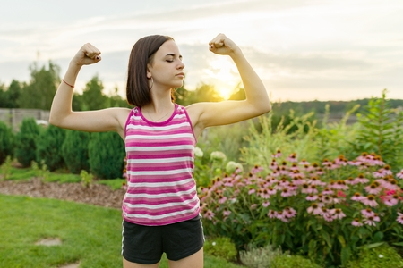 People, power, stamina, strength, health, sport, fitness concept. Outdoor portrait smiling teenage girl flexing her muscles, background green lawn sunset