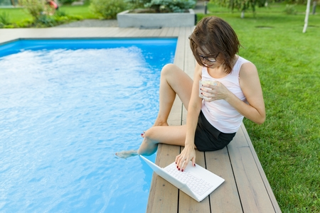 Mature woman freelancer uses a laptop sitting by the pool. Middle-aged woman blogger on a background of nature, yard, home pool is blogging