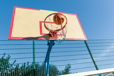 Street basketball, close-up of basketball ring and ball flying into the basket