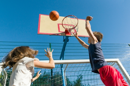 Streetball basketball game with two players, teenagers girl and boy, morning on basketball court Stock Photo