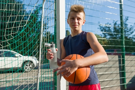 Teenager boy playing basketball with ball on the basketball court drinking water