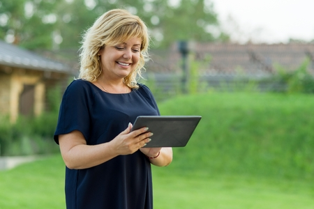 Outdoor portrait of mature business woman with digital tablet, background green garden of a private residence.