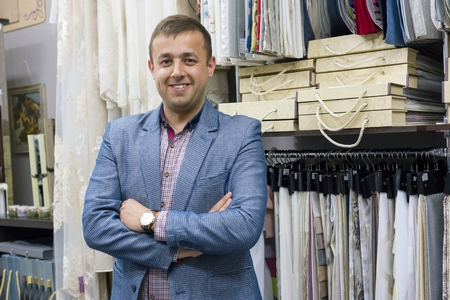 Portrait of happy businessman owner with crossed arms in interior fabrics store, background fabric samples. Small business home textile shop