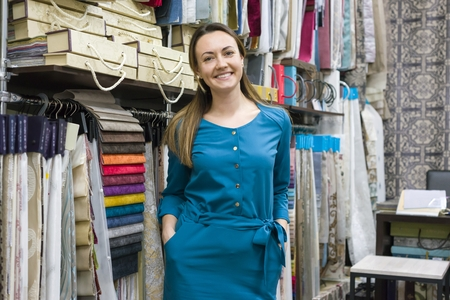 Portrait of happy mature woman owner in interior fabrics store, background fabric samples. Small business home textile shop Banco de Imagens
