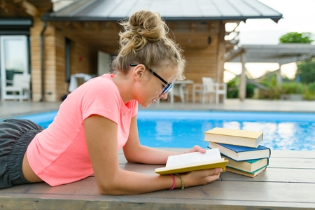 Young girl in glasses near the pool with a pile of books, reading book. Education, summer, knowledge
